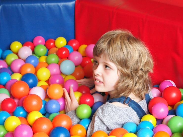 Image shows Chloe, a LOOK mentee, playing in a colourful ball pit. She is submerged up to her shoulders in multi-coloured balls with red and blue crash mat behind her.