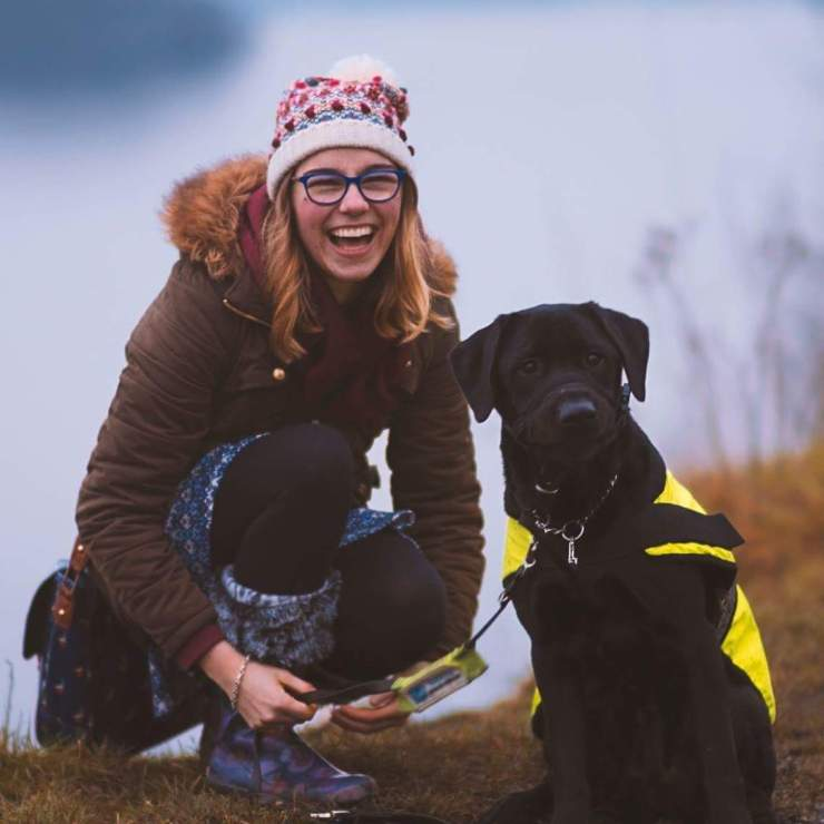 Image shows Look volunteer Kirsten smiling, wearing wellies in a field, with her guide dog.