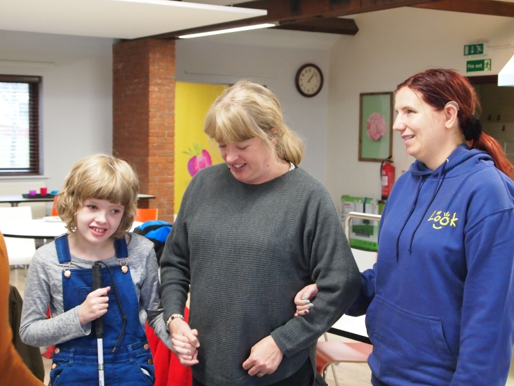Image shows Look volunteer Andrea arm in arm with mentee Chloe, aged ten and her mum.