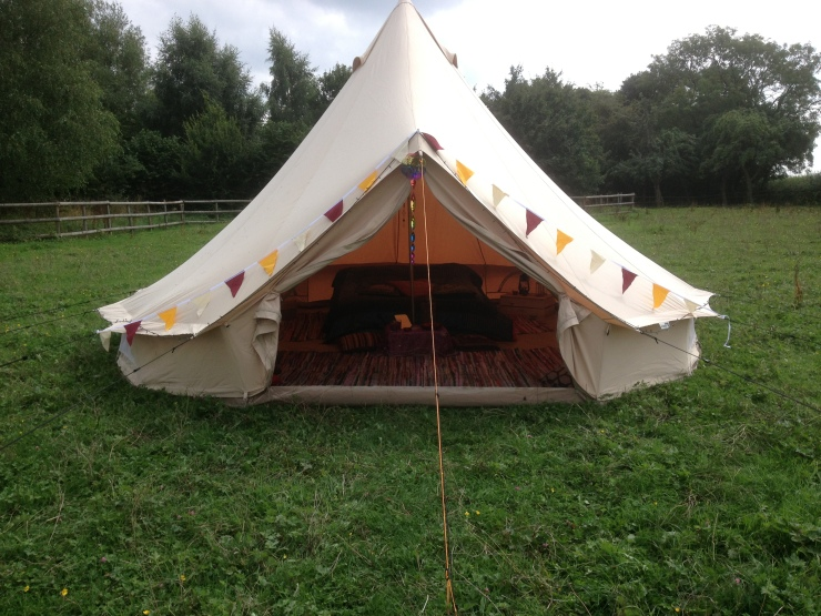 Image shows a small bell tent, furnished for two, with bunting around the door.
