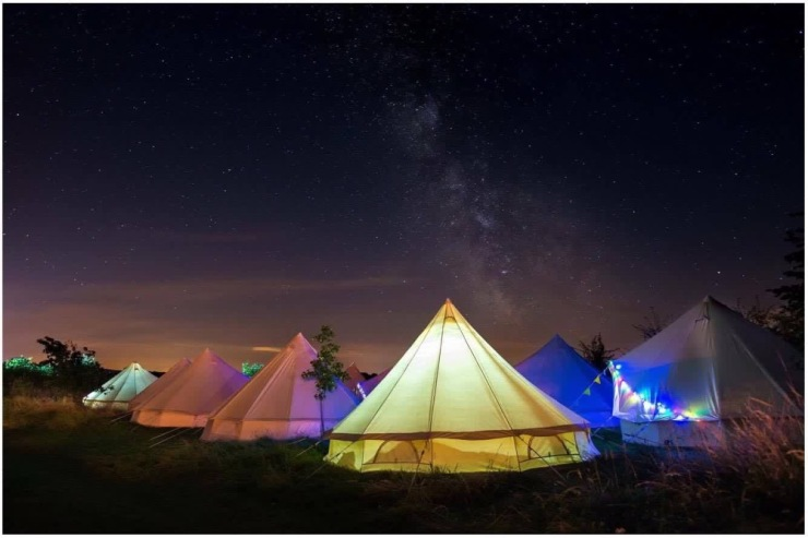 Image shows bell tents illuminated in different colours in a field at night with fairy lights