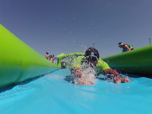 picture of a man diving head first down a slip and slide.
