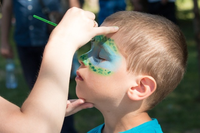 image of a boy having his face painted.