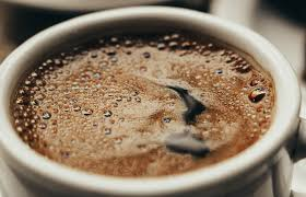 Close up image of black frothy coffee