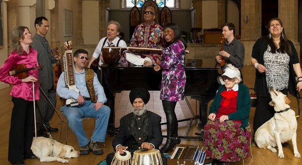 group photo of inner vision orchestra.  10 VI musicians and a guide dog smiling and laughing with their instruments .