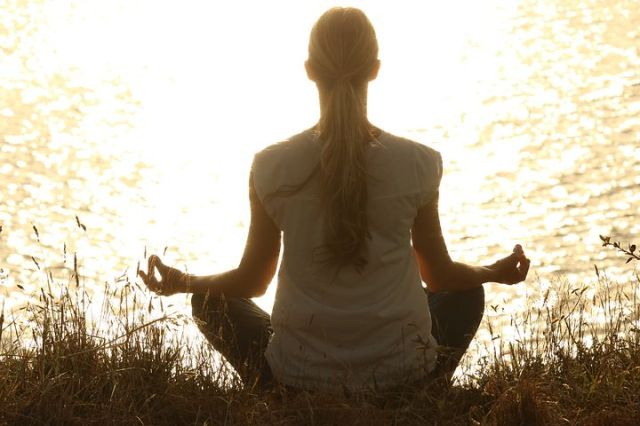 image of a woman meditating in front of open water.