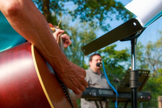 close up of guitar of a band playing in the outdoors.
