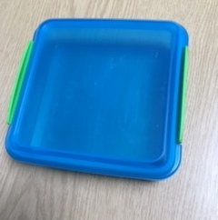 Empty Tupperware container in a square shape with a blue lid